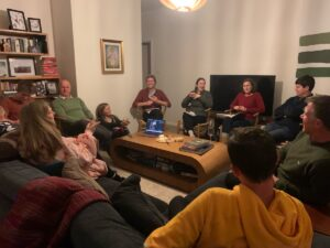 A group of people gathered in a circle in a living room