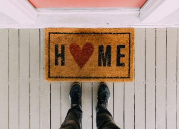 A door mat with the word home. The letter o has been replaced with a love heart.