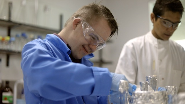A young man with Down syndrome wearing a lab coat and working in a lab