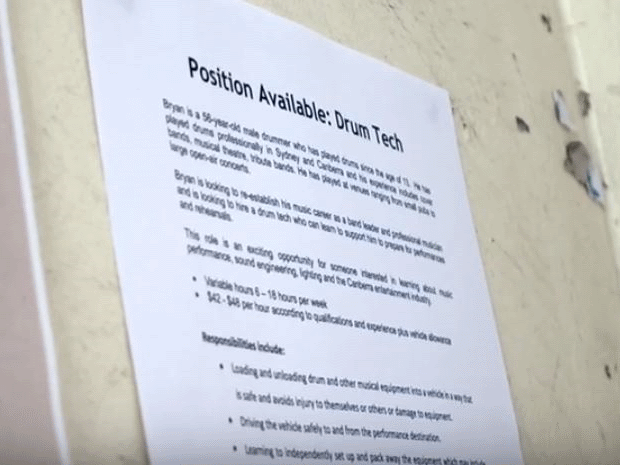 A job advertisement for a drum technician stuck to a wall