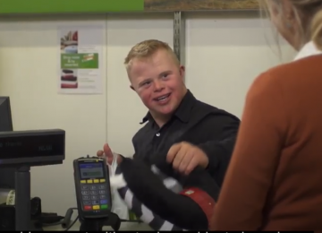 Young man serving at retail checkout.