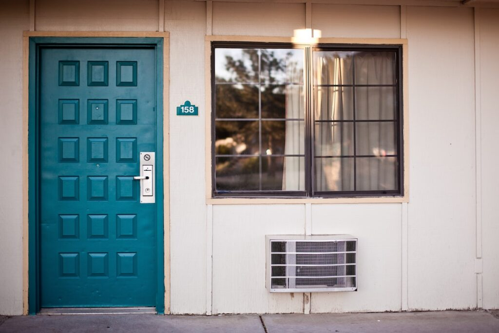 Teal wooden front door next to window