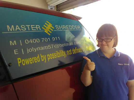 "Emma, the Master Shredder, standing next to her care, pointing to the signwriting, ""Powered by possibility, not defined by disability""."