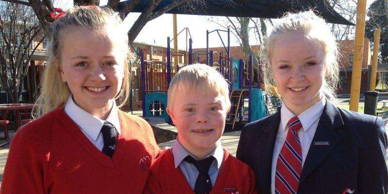 Three children in school uniform with a school playground in the background